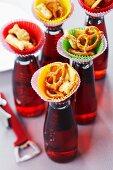 Mini tapas bar; snacks in paper cake cases on top of bottled drinks