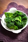 Blanched savoy cabbage on a plate with a spoon