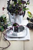 A name tag with aronia berries in a heart-shaped cookie cutter