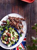 Grilled Australian lamb kebabs served with potato salad with green beans, avocado and bacon