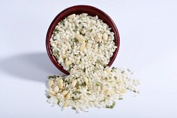 Vialone Nano risotto rice with pine nuts and chives in a ceramic bowl