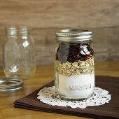 A jar containing dry ingredients for making oatmeal and cranberry biscuits