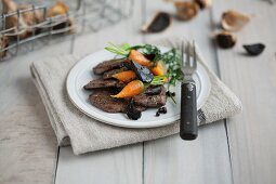 Beef fillet with baby carrots and black garlic