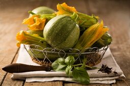 A still life featuring courgettes and courgette flowers in a wire basket