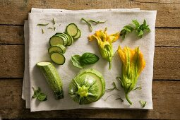 A still life featuring courgettes, courgette flowers and herbs
