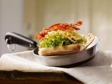 Baguette sandwich filled with scrambled egg, lettuce and crispy bacon