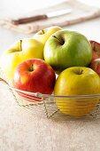 Verschiedene Äpfel in Drahtkorb