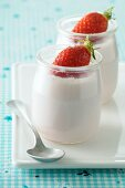 Natural yoghurt in glass pots, garnished with fresh strawberries