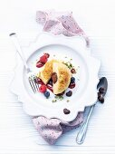 A sweet dumpling with a chocolate praline centre on berry sauce