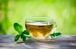 Peppermint tea on a wooden surface in the garden