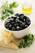 Black olives in a bowl, with bread and parsley