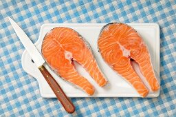 Two fresh salmon steaks on a chopping board with a knife