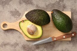 Fresh avocados on a chopping board with a knife