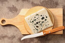 A wedge of blue cheese on a wooden board with a knife
