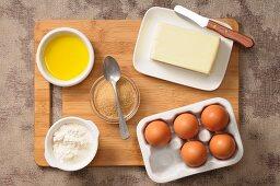 Assorted baking ingredients (eggs, sugar, butter, flour, olive oil)