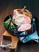 Stuffed leg of lamb and bacon-wrapped beans