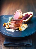 Medallion of venison wrapped in bacon with a cranberry-stuffed pear