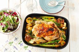 Roast chicken with garlic, asparagus, potatoes and apples