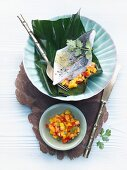 Sea bass fillet wrapped in banana leaf with mango-papaya salsa