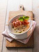 Garlic soup with pesto and bacon kebab
