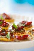 Mini pancakes with pesto, sundried tomatoes and basil