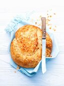 Almond knot loaf on a tea towel with a bread knife