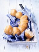 Party bread rolls on a tea towel with a bread knife