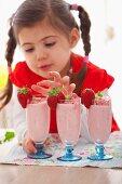 A girl with three strawberry milkshakes