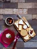 A cheeseboard with crackers and jam