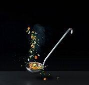 Gemischtes Gemüse fällt in eine Kelle mit Gemüsesuppe
