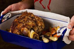 A man holding shin of veal in a roasting tin