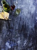 View onto a blue wooden table with olive oil, glasses of wine and forks on a wooden board