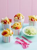 Honeydew melon granita with exotic fruit salad in paper ice cream tubs