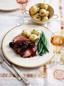 Crispy duck breast with cherry sauce, potatoes and beans