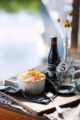 A mini fish bake in a ramekin on a wooden table laid with maritime decorations