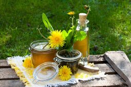Various dandelion products; jelly, liqueur and pickled buds on wooden boards