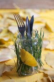 Jar decorated with pine needles and gingko leaf and used as cutlery holder