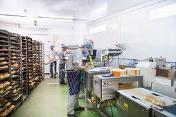 Workers at a bakery with shelves of bread and a packaging machine