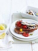 Slices of bread topped with marinated sardines and crushed roasted cherry tomatoes