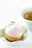 An iced profiterole with a cup of tea