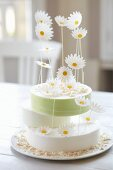 Three-tier lemon layer cake with oxeye daisies