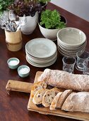 Stacks of crockery and glasses on a table with ciabatta bread on a wooden board