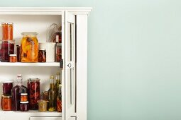 Preserved fruit in jars and bottles in an open kitchen cabinet