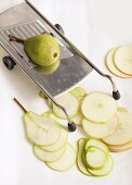 Apples and pears being finely sliced on a mandolin