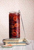Stewed damsons with port in a preserving jar