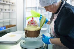 A pastry chef decorating a giant cupcake