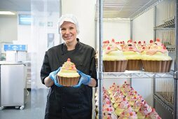 A pastry chef with giant cupcakes