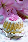 A mini Bundt cake with icing sugar and flower decoration