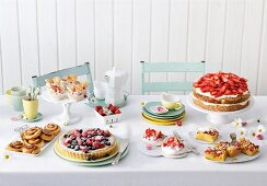 A cake buffet with berry cakes and tarts and sweet pastries