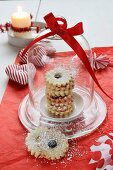 Jam-filled ring biscuits under a glass dome, a fabric heart and a candle